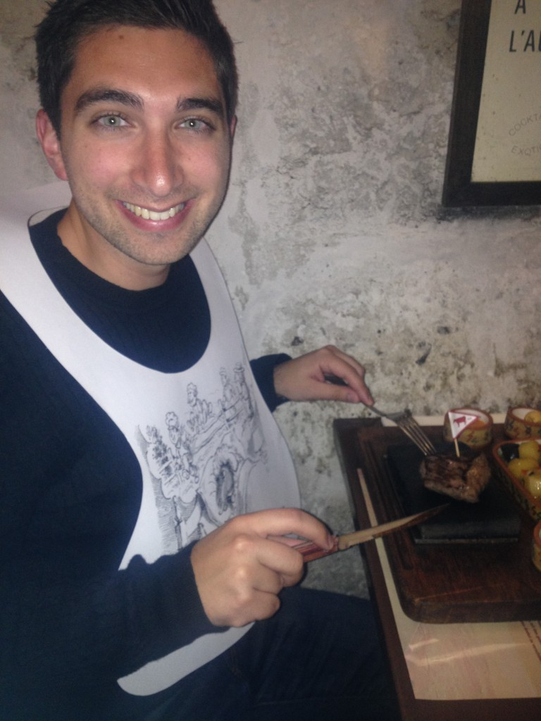Eating a piece of beef cooking and sizzling on a volcanic stone. And yes, they gave me a bib.