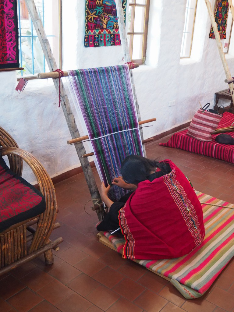 A local woman completing some a Tarabuco weaving at the Museo de Arte Indigena